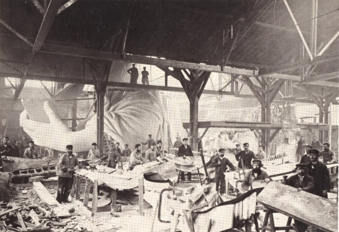 A team of workers hammering sheets of copper during construction