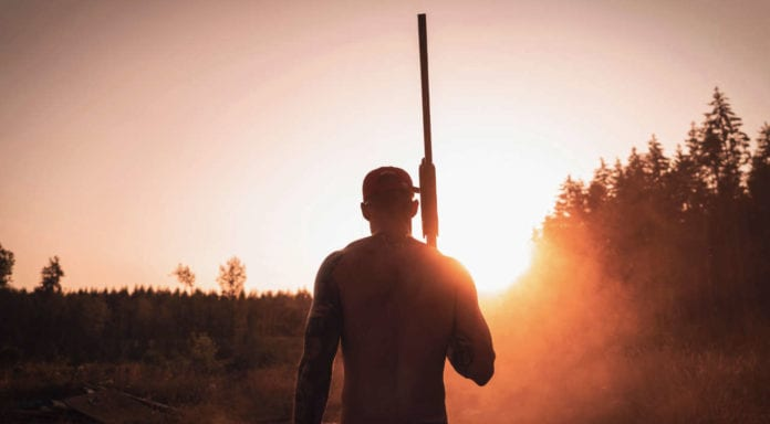 Silhouette of man holding rifle