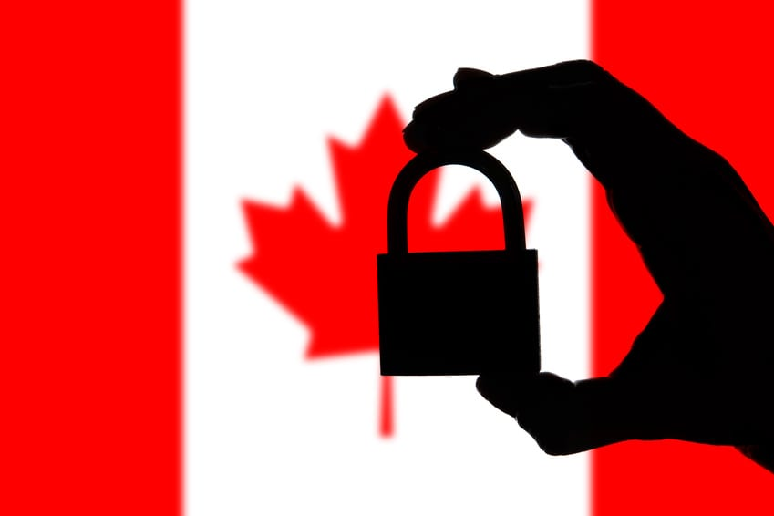 Canada security. Silhouette of hand holding a padlock over national flag